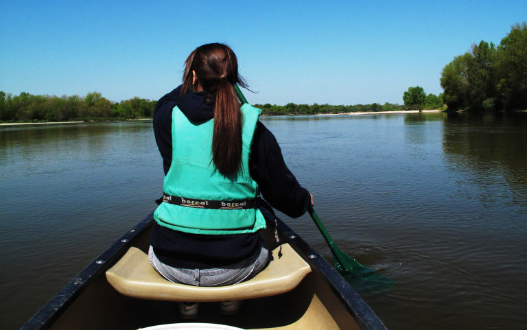 A woman in a canoe rows forward into a brighter future - the aim of our programme Bede: Ending Domestic Abuse.
